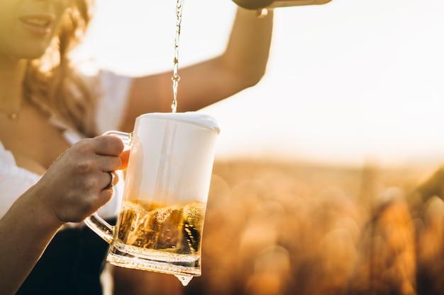 Nahaufnahme der mädchenhände im dirndl, der ein volles glas bier mit riesigem schaum im freien einschenkt