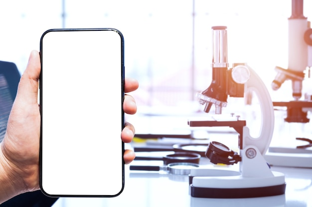 Nahaufnahme der männer verwenden smartphone unscharfe bilder von mikroskopen und reagenzgläsern mit laborglaswaren im laborhintergrund, forschung und wissenschaftlichem konzept