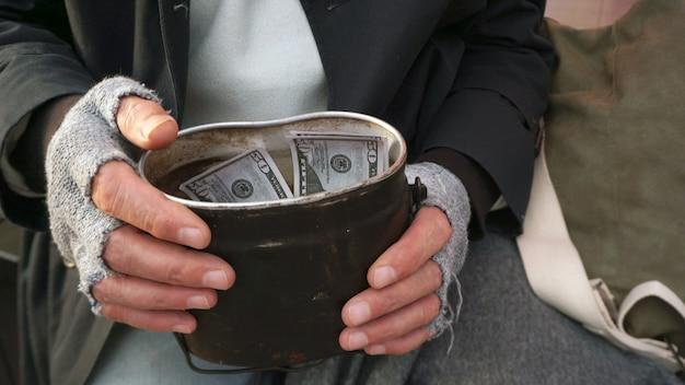Nahaufnahme der männerhände, die finanzielle hilfe, dollar halten. obdachloser, alter mann, der dollars in der hand hält
