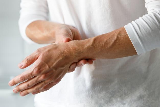 Nahaufnahme der männlichen arme, die ihr schmerzhaftes handgelenk halten, verursacht durch längere arbeit am computer, laptop. karpaltunnelsyndrom, arthritis