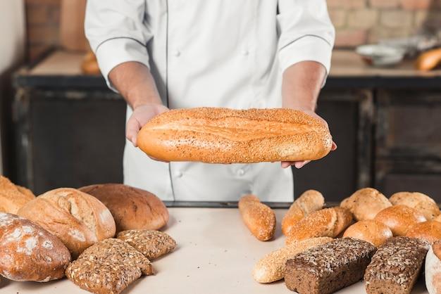 Nahaufnahme der männlichen bäckerhände, die frisches brot halten