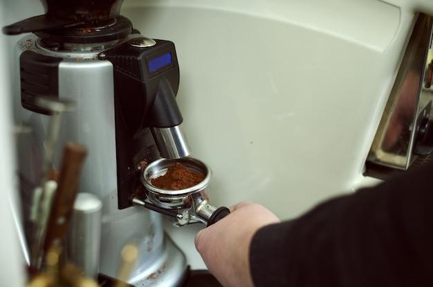 Nahaufnahme der männlichen barista-hand, die gemahlenen kaffee für die zubereitung von espresso hält