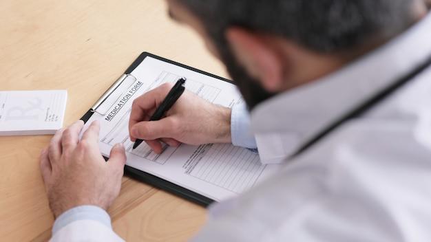 Nahaufnahme der männlichen hände der ärzte, die patientendaten in medizinischer form in der arztpraxis schreiben.