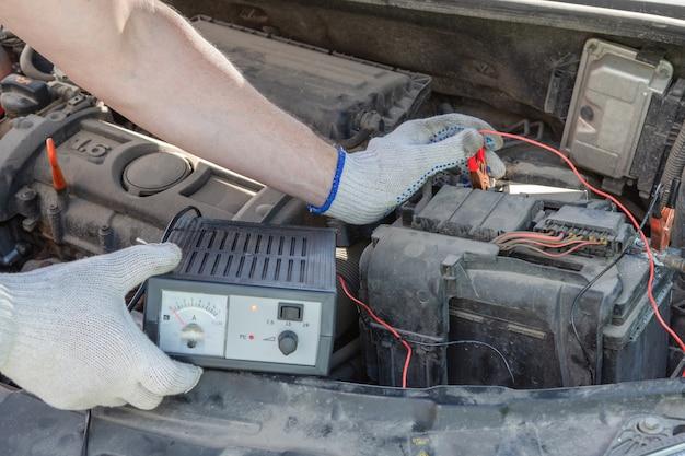 Nahaufnahme der männlichen hände, die die spannung der autobatterie unter der motorhaube überprüfen