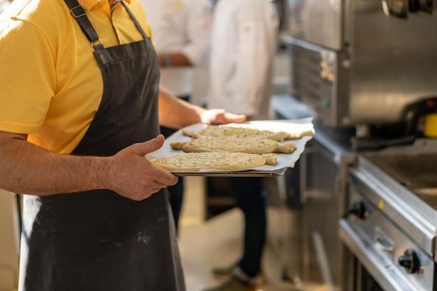 Nahaufnahme der männlichen hände, die ein tablett mit khachapuri halten und sich vorbereiten, zum ofen zu senden. traditionelles georgisches käsebrot. georgisches essen