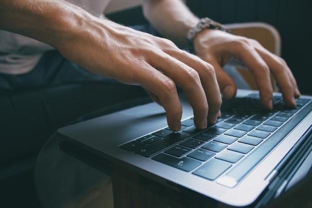 Nahaufnahme der männlichen hände, die textnachricht auf laptoptastatur eingeben, junger männlicher freiberufler, der von zu hause aus arbeitet
