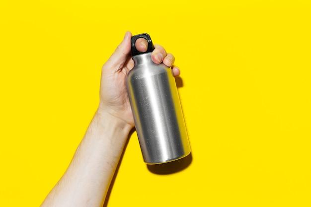 Nahaufnahme der männlichen hand, die aluminium, thermowasserflasche auf dem hintergrund der gelben farbe hält.