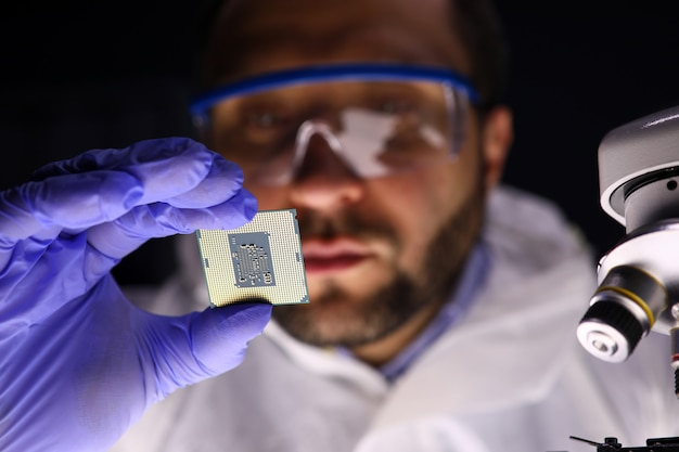 Nahaufnahme der männlichen hand, die computer-mikroschaltung hält. professioneller techniker, der mikrochip mit mikroskop untersucht. computerelektronik und technikkonzept