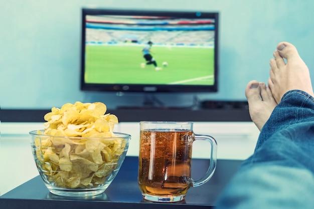 Nahaufnahme der männlichen hand, die eine tasse bier hält, mit gekreuzten füßen vor einem großen fernseher, der in seinem wohnzimmer sitzt und fußball guckt. fan, der die tv-meisterschaft auf dem kanal sieht.