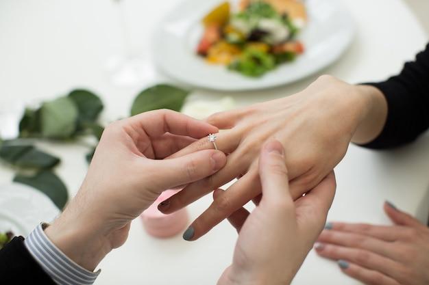 Nahaufnahme der männlichen hand, die einen verlobungsring in einen finger einfügt