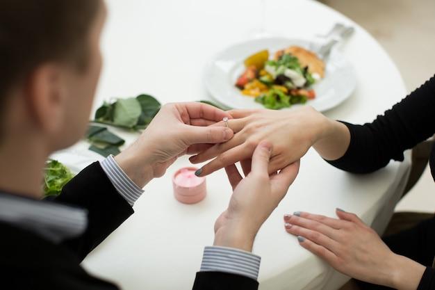 Nahaufnahme der männlichen hand, die einen verlobungsring in einen finger einführt