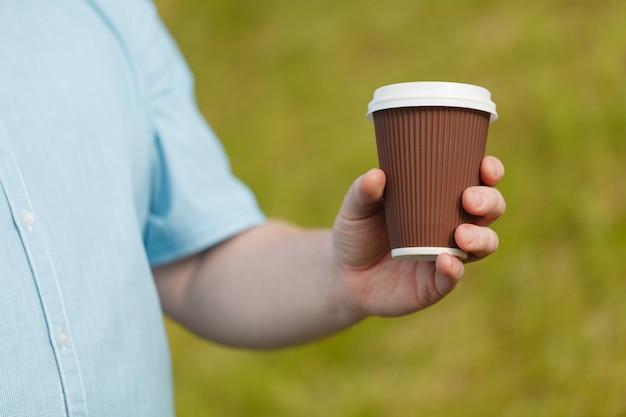Nahaufnahme der männlichen hand, die kaffee hält, um wegzunehmen