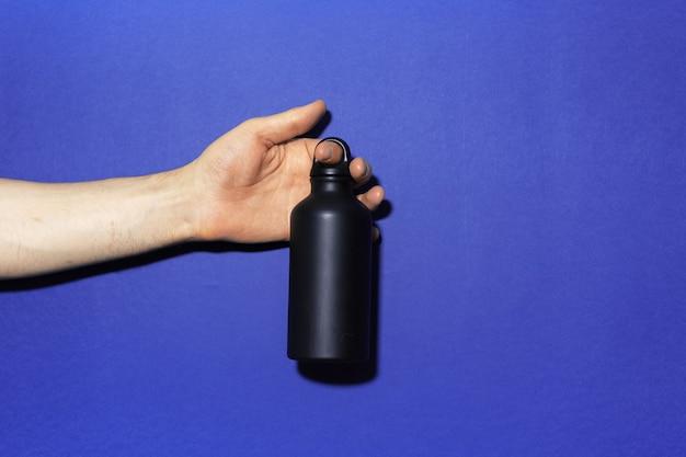 Nahaufnahme der männlichen hand, die schwarze wiederverwendbare aluminium-thermowasserflasche auf hintergrund der phantomblauen farbe mit kopienraum hält.