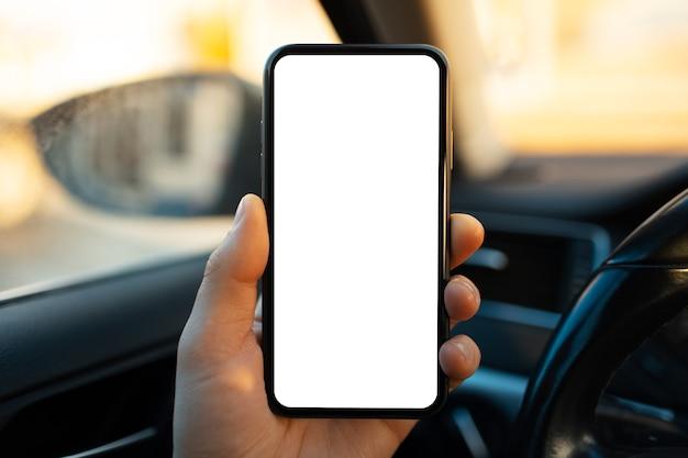 Nahaufnahme der männlichen hand, die smartphone mit weißem modell auf bildschirm gegen unscharfen hintergrund des autoinnenraums hält.