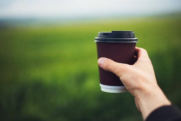 Nahaufnahme der männlichen hand, die wegwerfbare papierkaffeetasse auf hintergrund des unscharfen grünen grases hält.