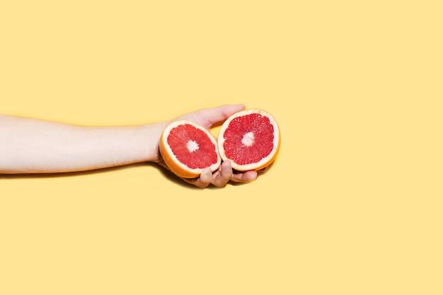Nahaufnahme der männlichen hand, die zwei hälften der grapefruit hält
