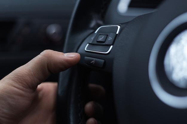 Nahaufnahme der männlichen hand drückt knopf des telefons am lenkrad des autos.