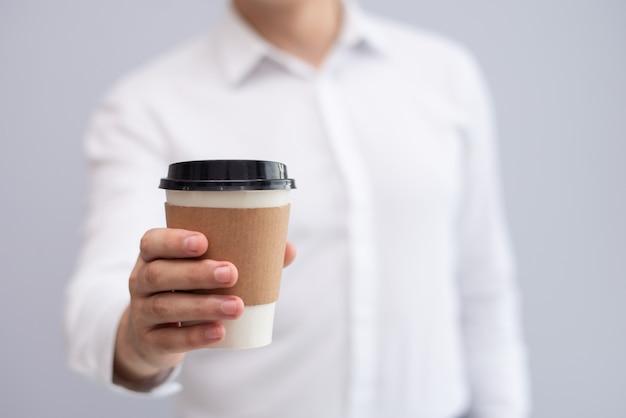 Nahaufnahme der männlichen hand mitnehmerkaffee halten