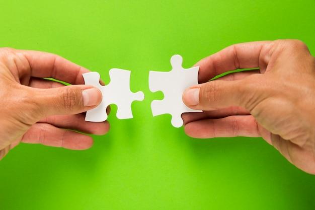 Nahaufnahme der männlichen hand weißes puzzlestück über grünem hintergrund verbindend