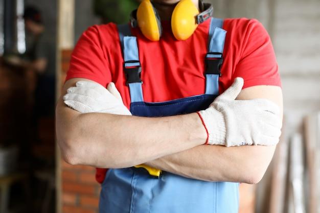 Nahaufnahme der männlichen person, die mit gefalteten händen steht. professioneller baumeister im spezialkesselanzug