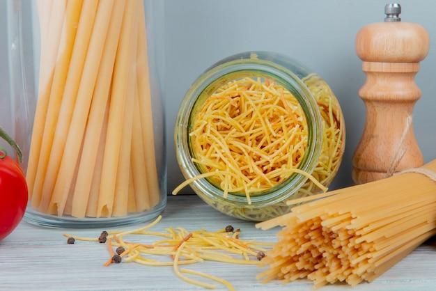 Nahaufnahme der makkaronis als bucatini-spaghetti-fadennudeln mit salz auf holzoberfläche und blauer oberfläche