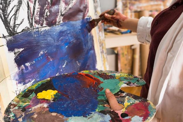 Nahaufnahme der malerei der frau hand auf segeltuch mit dem halten der unordentlichen palette
