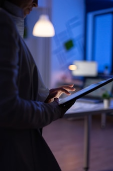 Nahaufnahme der managerfrau, die auf dem tablett schreibt und finanzdiagramme überprüft, die im start-up-büro stehen