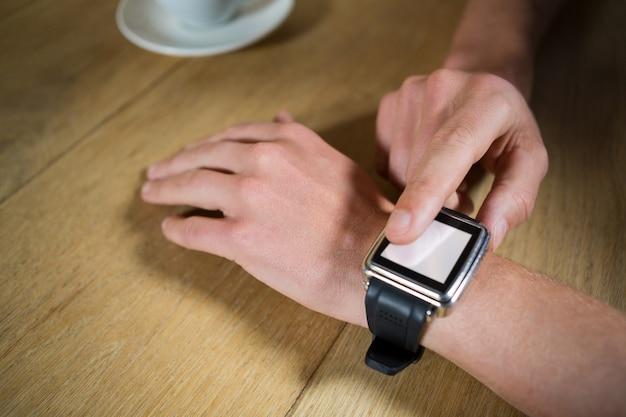 Nahaufnahme der mannhände unter verwendung der intelligenten uhr am tisch im kaffeehaus
