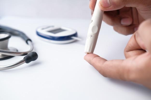 Nahaufnahme der mannhand, die diabetiker auf tisch misst