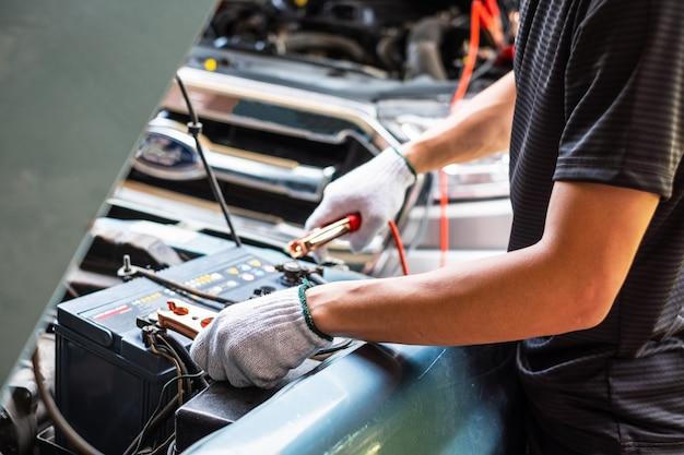 Nahaufnahme der mannhand, die eine autobatterie auflädt