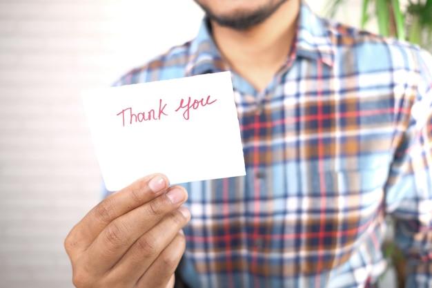 Nahaufnahme der mannhand, die einen dankesbrief liest