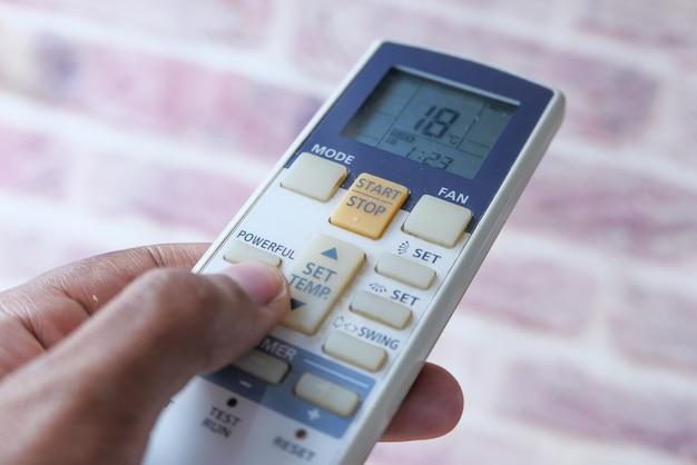 Nahaufnahme der mannhand, die klimaanlagenfernbedienung hält.