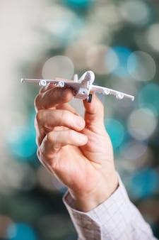 Nahaufnahme der mannhand, die modell des flugzeugs auf einem weihnachtshintergrund hält