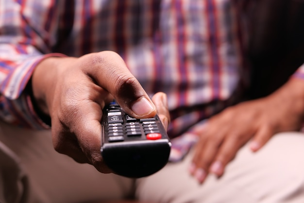 Nahaufnahme der mannhand, die tv-fernbedienung hält.