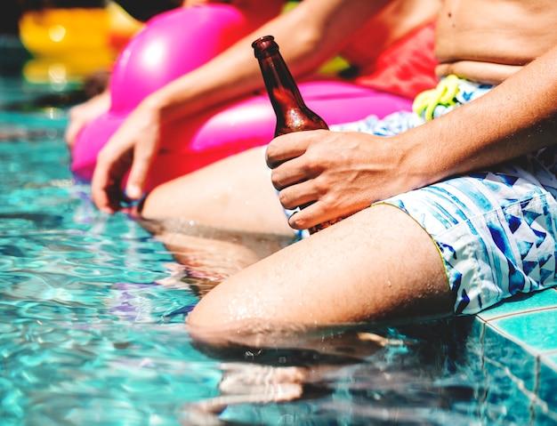 Nahaufnahme der mannhand eine bierflasche durch die poolseite halten