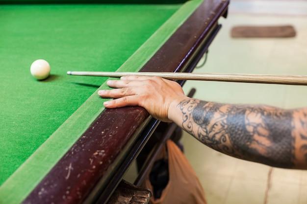 Nahaufnahme der mannhand mit billardstichwort bereit, weißen ball zu schlagen