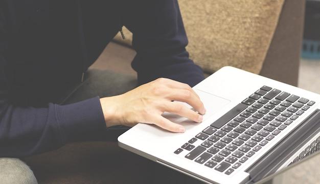 Nahaufnahme der mannhand unter verwendung des laptops und der schreibentastatur.