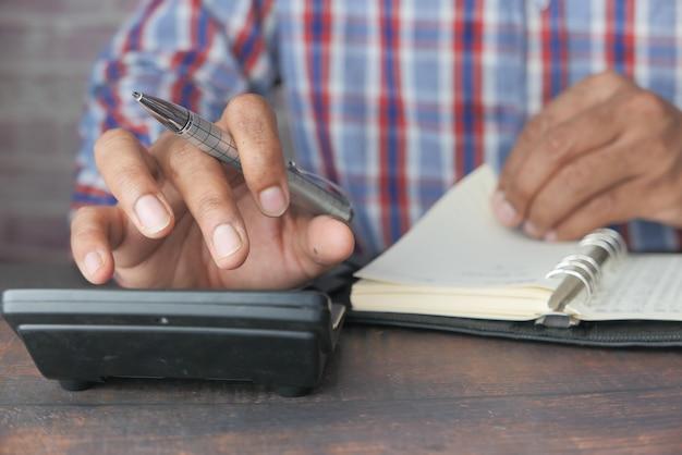 Nahaufnahme der mannhand unter verwendung des taschenrechners