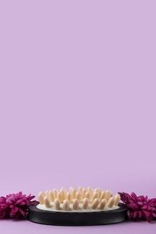 Nahaufnahme der massagebürste mit zwei schönen blumen gegen purpurroten hintergrund