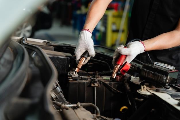 Nahaufnahme der mechanischen hand, die die batterie eines autos mit strom durch überbrückungskabel auflädt, batterieinspektion