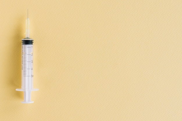 Nahaufnahme der medizinischen spritze auf gelbem strukturiertem hintergrund