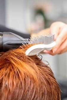 Nahaufnahme der meisterhand mit föhnen und haarbürste, die weibliches rotes haar in einem salon weht
