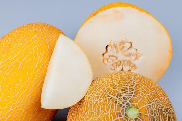 Nahaufnahme der melonenscheibe mit geschnittenen und ganzen auf bläulich grauem hintergrund