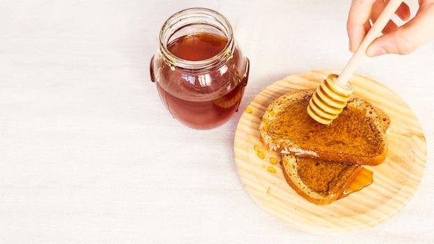 Nahaufnahme der menschlichen hand honig auf brot unter verwendung des honigschöpflöffels ausbreitend
