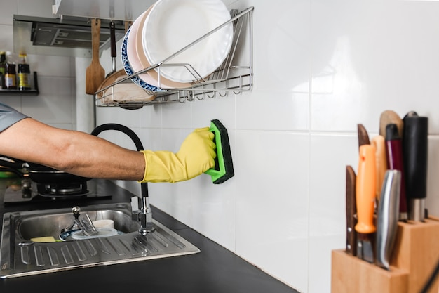 Nahaufnahme der menschlichen hand in einem gelben gummihandschuh verwendet eine plastikbürste, um die fliesenwand im küchenraum zu schrubben.