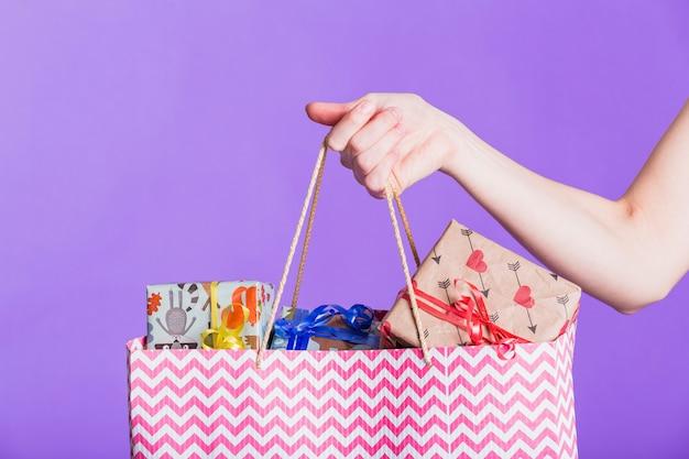 Nahaufnahme der menschlichen hand papiertüte mit eingewickeltem geschenk halten