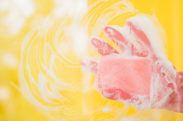 Nahaufnahme der menschlichen hand rosa handschuhe tragend, die gelben hintergrund mit seifenlauge waschen