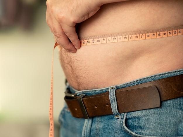 Nahaufnahme der messung eines männlichen bauches mit einem schneidermeter. der mann zeigt seinen nackten bauch