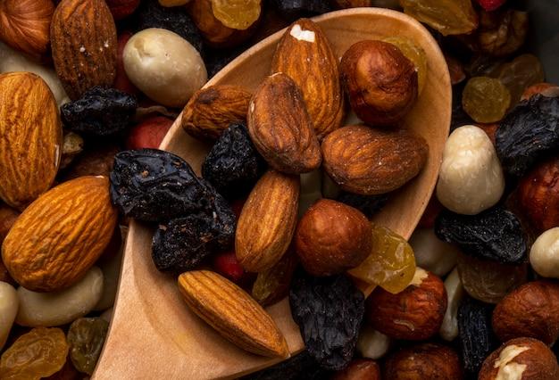 Nahaufnahme der mischung von nüssen und getrockneten früchten mandel und schwarzen rosinen
