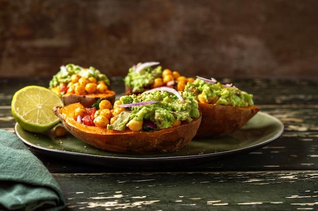 Nahaufnahme der mit tomaten, kichererbsen, zwiebeln und avocado gefüllten kartoffel.